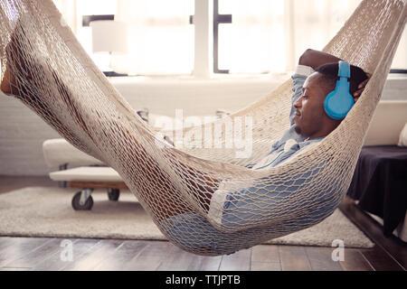 L'homme à l'écoute de la musique tout en se reposant sur l'hamac dans la salle de séjour à la maison Banque D'Images