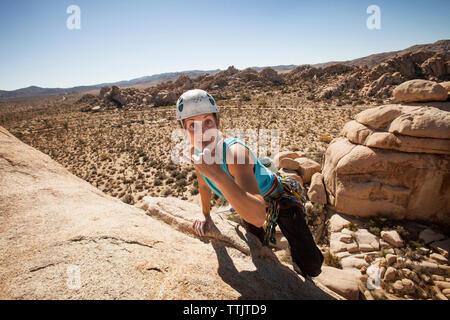 Portrait of happy woman gesturing alors que l'escalade rock formation against sky Banque D'Images