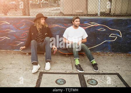 Friends sitting on skateboard in park Banque D'Images