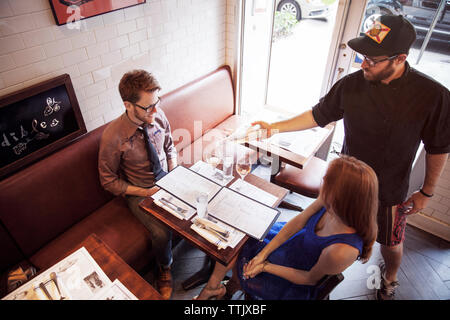Waiter pouring wine pour couple sitting in restaurant Banque D'Images