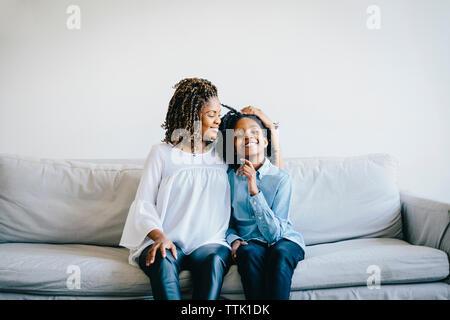 Portrait of happy daughter sitting avec mère enceinte sur canapé à la maison