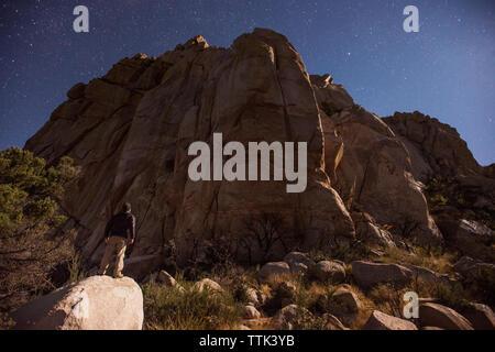 Low angle view of hiker debout sur rock en regardant le ciel étoilé contre la montagne Banque D'Images