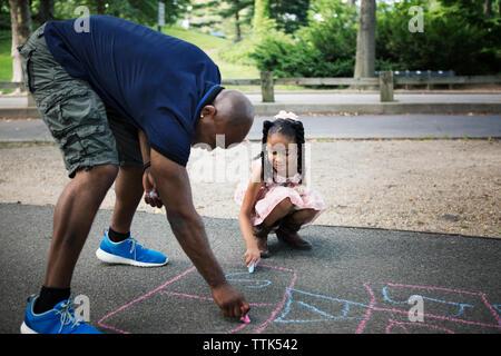 Père et fille de marelle dessin sur route à park Banque D'Images