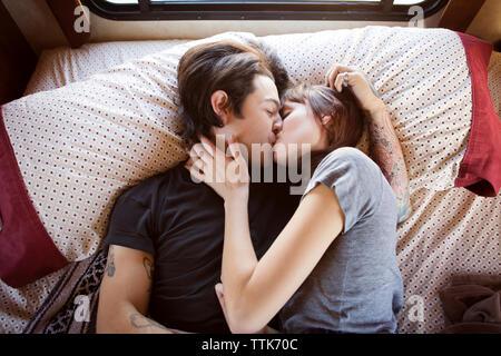 Couple en position allongée sur lit dans le camping-car Banque D'Images