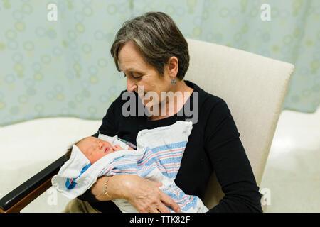 Grand-mère regarde souriant à nouveau-né petit-enfant en chambre d'hôpital Banque D'Images