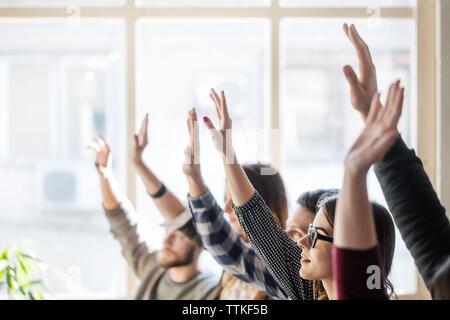 Sensibilisation des élèves pendant la leçon en classe les mains Banque D'Images