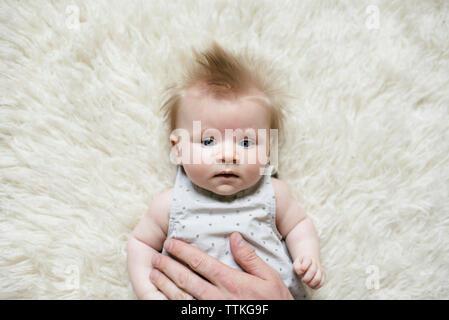 Portrait de la main touchant père fille couchée sur un tapis à poils à la maison Banque D'Images