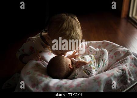 Frère soeur s'embrasser sur le front de dormir dans le panier de Moïse à la maison Banque D'Images