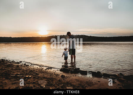 Avec Père Fils debout dans le lac contre ciel nuageux pendant le coucher du soleil Banque D'Images