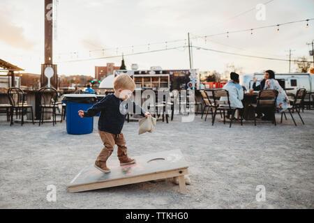 Toute la longueur de baby boy standing on wooden board at sidewalk cafe pendant le coucher du soleil Banque D'Images