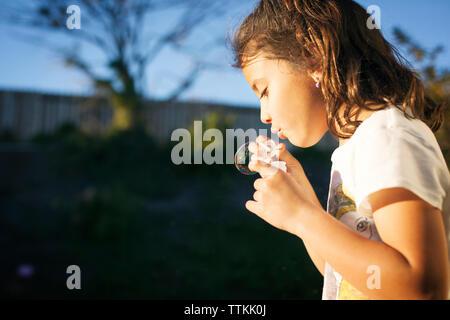 Close-up of girl blowing bubble avec baguette sur sunny day Banque D'Images