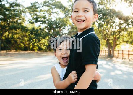 Portrait of happy soeur avec bouche ouverte embrassant frère en se tenant sur le road contre des arbres en parc