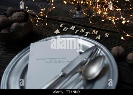 Portrait de couverts avec la plaque par les noix et les décorations de Noël sur la table en bois Banque D'Images
