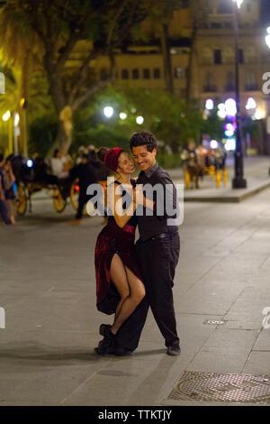 Un couple danse dans les rues de Sevilla Banque D'Images