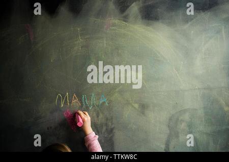 Portrait of Girl drawing on blackboard Banque D'Images