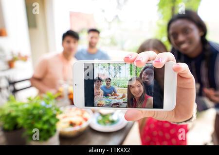 Multi-ethnic friends at outdoor table du déjeuner selfies Banque D'Images