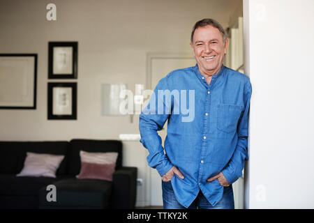 Portrait of happy senior man standing with hands in pockets at home Banque D'Images