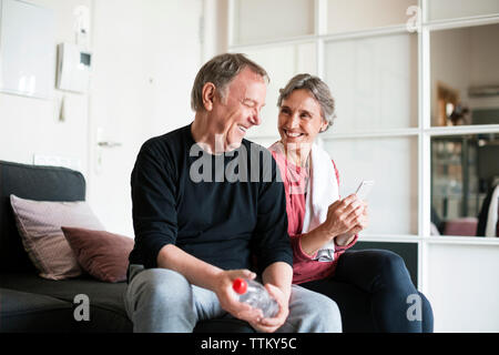 Happy senior couple using smart phone in living room Banque D'Images