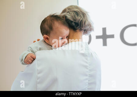 Vue arrière du médecin exerçant son bébé garçon contre le mur à l'hôpital Banque D'Images