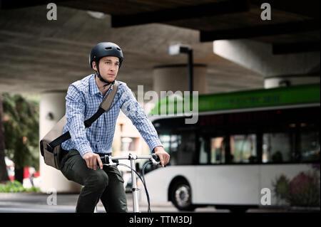 Businessman riding bicycle on city street