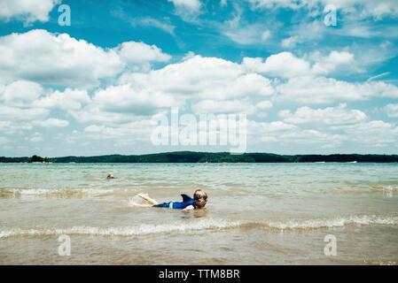 Garçon portant des lunettes de natation tout en se trouvant en mer contre ciel nuageux Banque D'Images