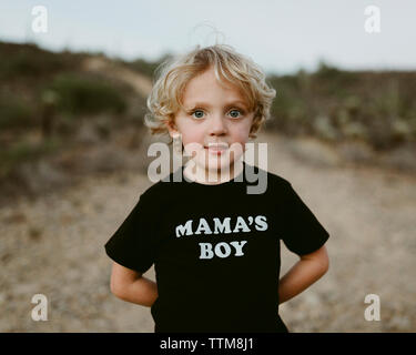 Portrait of cute boy standing on field against sky Banque D'Images