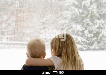 Vue arrière de la fratrie à la fenêtre pendant l'hiver grâce à Banque D'Images