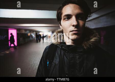 Close-up of young man wearing vêtements chauds tout en regardant ailleurs au passage souterrain dans la ville Banque D'Images