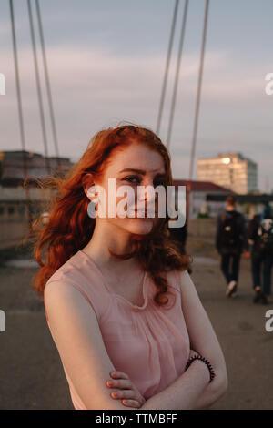 Portrait of young woman with arms crossed standing sur bridge en ville