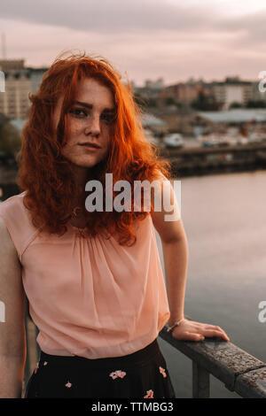 Portrait de jeune femme aux cheveux rouges l'article by railing on bridge