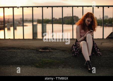 Jeune femme rousse à l'aide de téléphone mobile tout en restant assis sur le pont en ville
