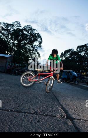 PHILIPPINES, Palawan, Puerto Princesa, garçon ne astuces sur son vélo dans le centre de Puerto Princessa près de l'Amphithéâtre Mitra Banque D'Images