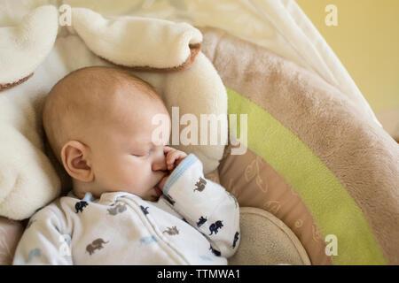 High angle view of baby boy sucking thumb pendant le sommeil dans la couchette Banque D'Images