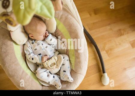 High angle view of baby boy sucking thumb pendant le sommeil en berceau à la maison Banque D'Images