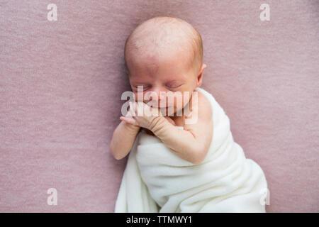Naissance bebe Fille en blanc portant clôture sur une couverture Rose, sucking Thumb Banque D'Images