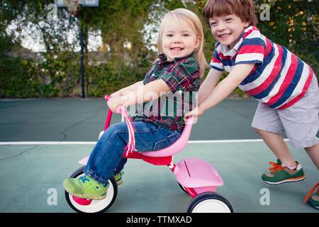 Portrait of happy boy poussant soeur assis sur tricycle at yard Banque D'Images