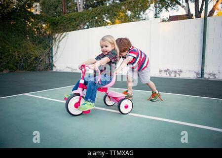 Garçon assis sur soeur poussant à tricycle yard Banque D'Images