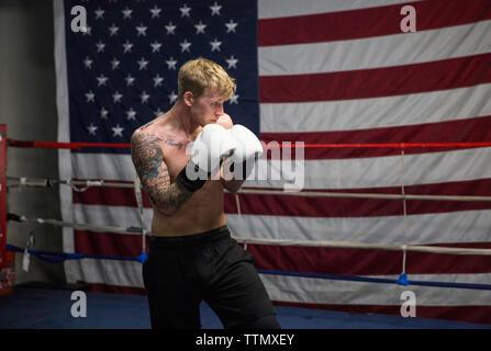 Shirtless boxer exerçant en ring de boxe contre drapeau Américain Banque D'Images
