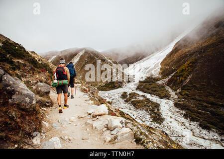 Vue arrière d'amis avec des sacs à dos randonnée au Parc national de Sagarmatha au cours de temps de brouillard Banque D'Images