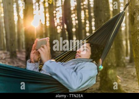 Woman using mobile phone while hamac en forêt durant le coucher du soleil