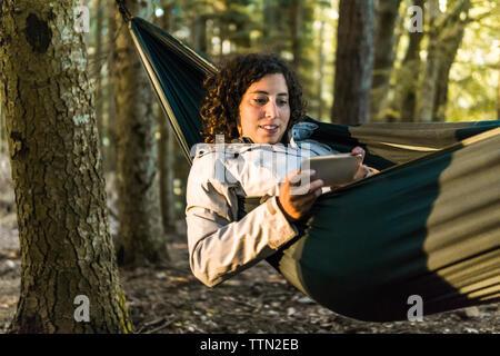 Femme à l'aide de smart phone en position allongée sur un hamac en forêt