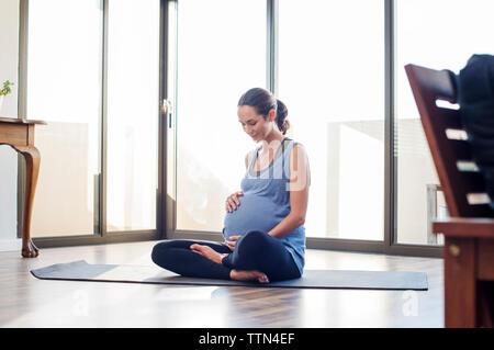 Pregnant woman holding abdomen tout en restant assis sur tapis d'exercice à la maison Banque D'Images