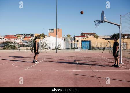 Teenage boy throwing ball en basket-ball alors que coach debout à cour Banque D'Images