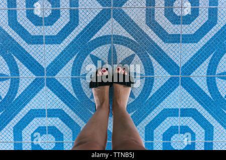 La section basse de femme portant des sandales en se tenant sur le carrelage Banque D'Images