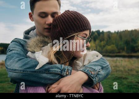 Faire place au petit ami petite amie en se tenant contre ciel nuageux dans la forêt Banque D'Images