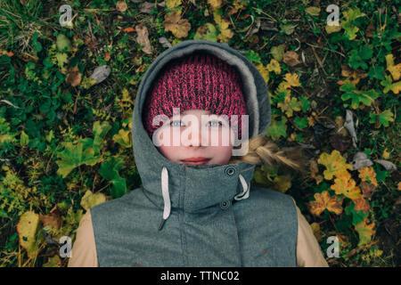 Jeune femme allongée sur l'herbe dans des vêtements chauds Banque D'Images