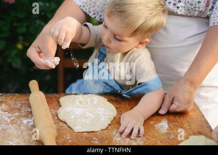 Portrait de Mère avec fils de préparer de la nourriture sur table en bois at yard Banque D'Images