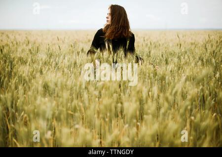 Jeune femme se trouve dans un champ de blé en été