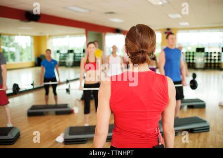 Vue arrière avec les clients de l'instructeur le barbell levage par étapes dans un club de santé Banque D'Images