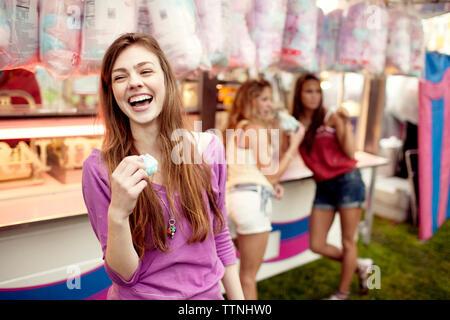 Teenage girl holding Cotton Candy avec des amis en arrière-plan Banque D'Images